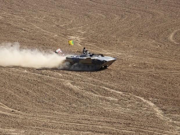 Integrante da Força de Mobilização Popular corre em tanque durante operação no sul de Mossul, na segunda-feira (31) (Foto: Reuters)