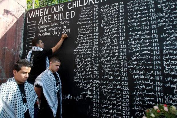 Jovem palestino anota nome de criança morta durante conflito entre forças israelenses e do Hamas (Foto: Musa Al Shaer/AFP)