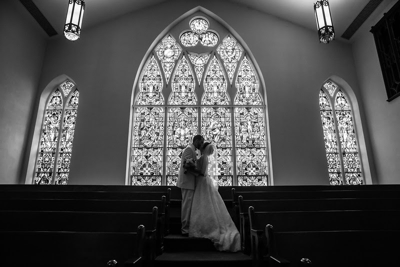 Photos of the bride and groom standing in front of a giant stained glass window at Court Street United Methodist Church in downtown Rockford Illinois for an Autumn wedding.