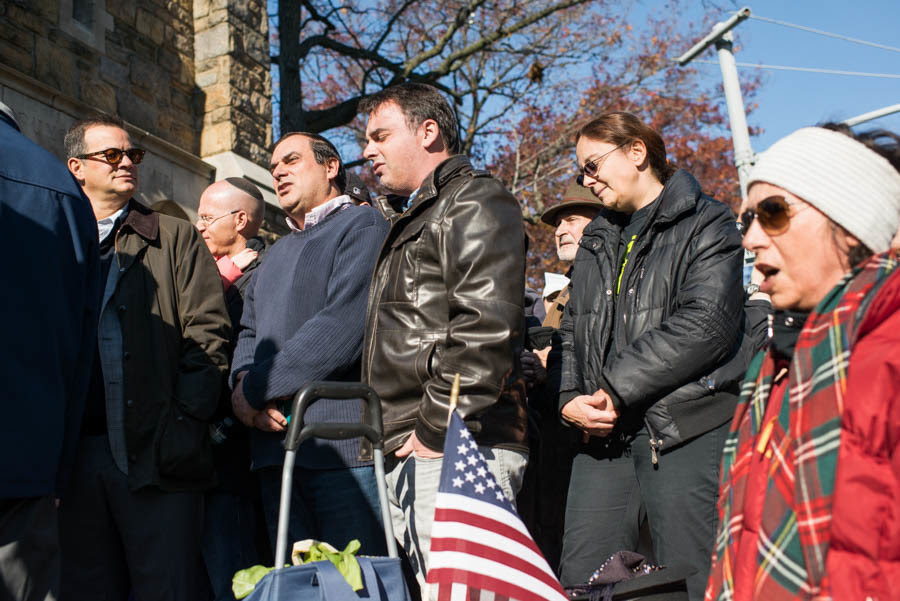Several Riverdale residents originally from France sing the French national anthem, 'La Marseillaise,'  at the rally.