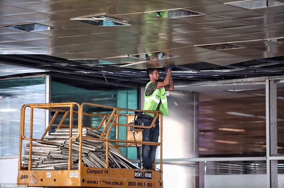 Um trabalhador repara o dano a um limite que tinha sido explodido quando um suicida detonou seus explosivos na porta do terminal de chegadas