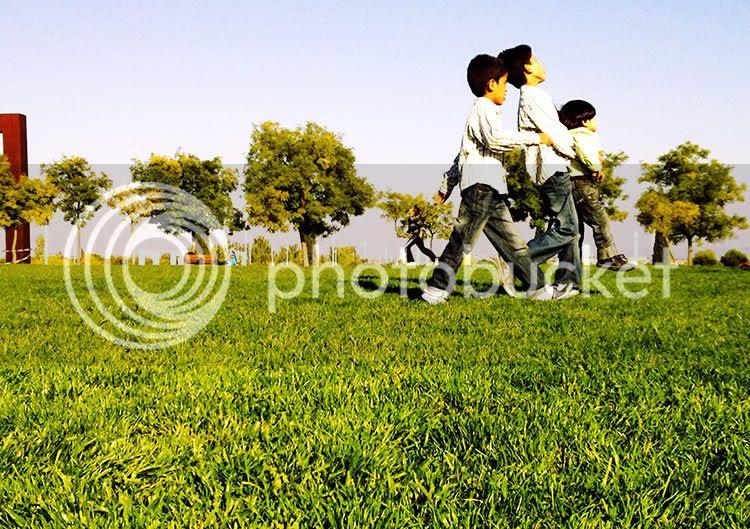 Tres niños van caminando en la misma dirección sobre el cesped