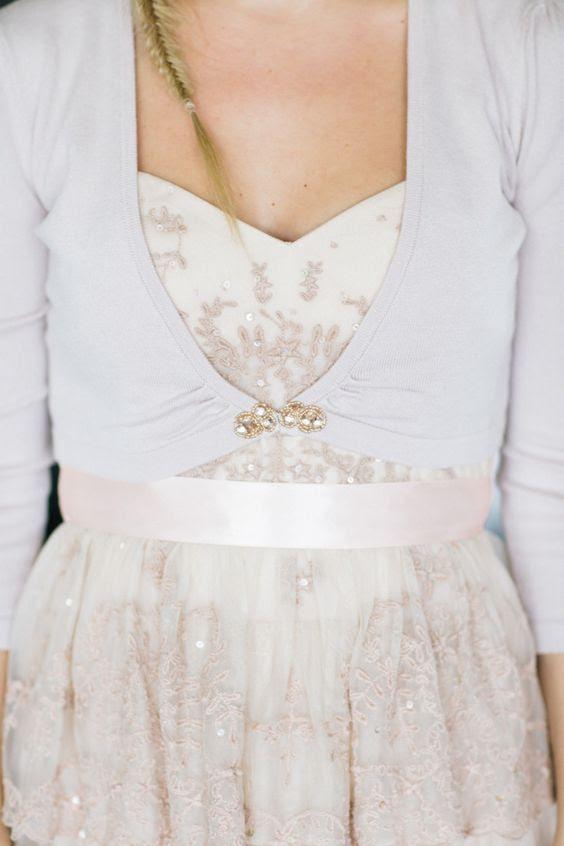 eine Neutrale cropped cardigan mit cropped ärmeln und einem glitzernden Brosche mit Strass
