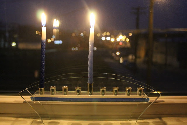 Menorah on the first night of Hanukkah and lights out the window