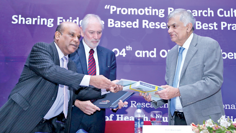 The Deputy Director General of Education Training and Research of the Health Ministry Dr. Sunil De Alwis presents the Abstract Book to Prime Minister Ranil Wickremesinghe while Prof. Alan Lopez looks on. Picture by Hirantha Gunathilaka