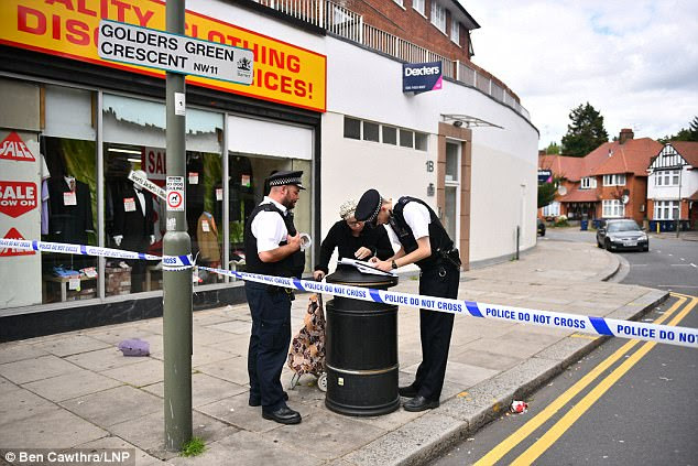 Police officers question residents in Golders Green Crescent, the scene of a double murder