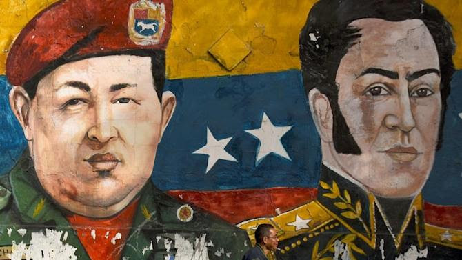 A mural of late Venezuelan president Hugo Chavez (left) and XIX century hero Simon Bolivar on a wall in the low-income Petare neighborhood