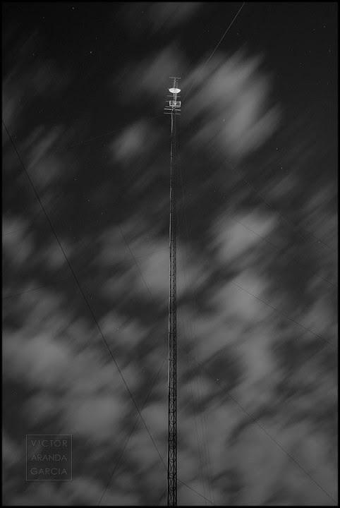 Antena con tirantes y nubes movidas de noche