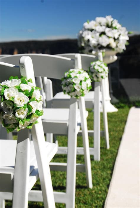 Ailse chairs decorated with white silk flower balls. #