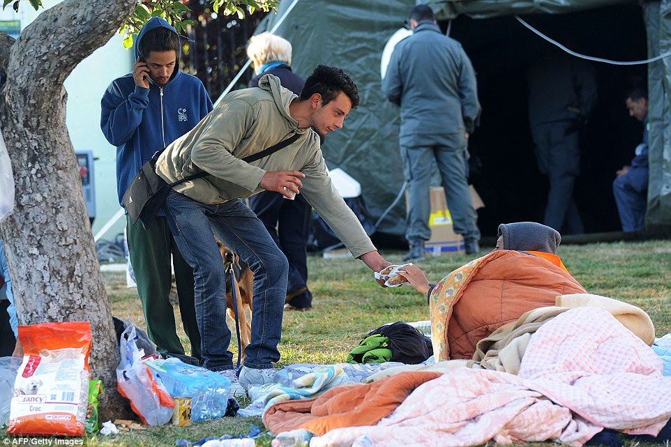 Earthquake survivors share food as they emerge from makeshift shelters and tents in a temporary encampment on open ground in the central Italian village of Amatrice