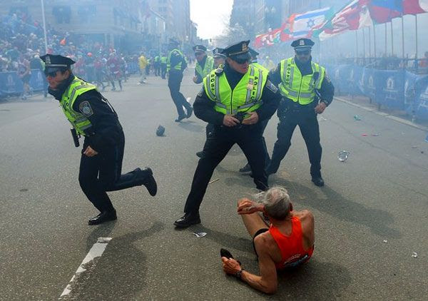 Police officers stand guard near a fallen runner after an explosion takes place at the Boston Marathon on April 15, 2013.