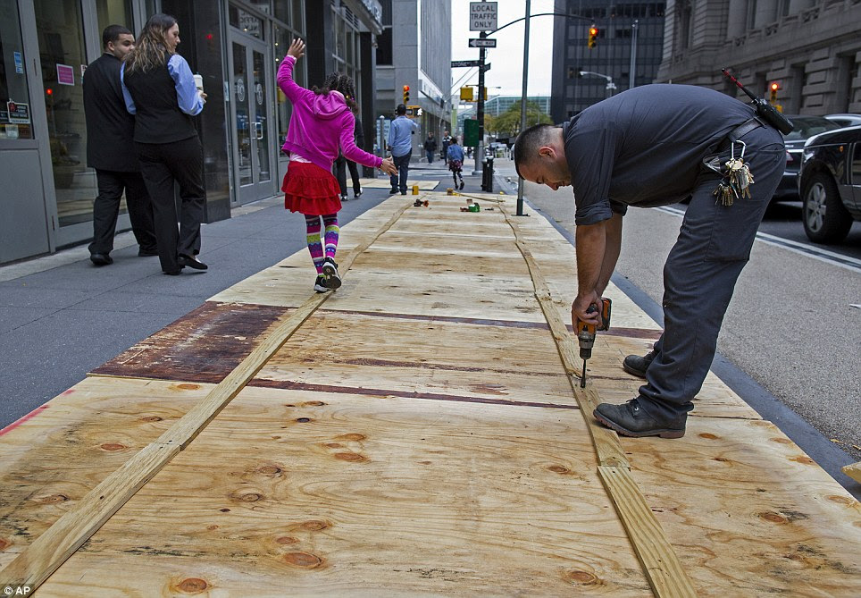 A maintenance worker attaches plywood to a sidewalk grate at the 2 Broadway building of Lower Manhattan in New York on Sunday in anticipation of the arrival of the megastorm