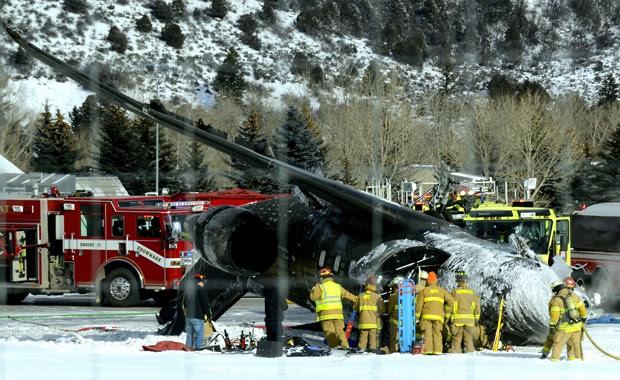 Equipe de emergência próxima a aeronave que caiu e pegou fogo ao pousar no aeroporto de Aspen, nos EUA, neste domingo (5) (Foto: AP Photo/The Aspen Times, Leigh Vogel)