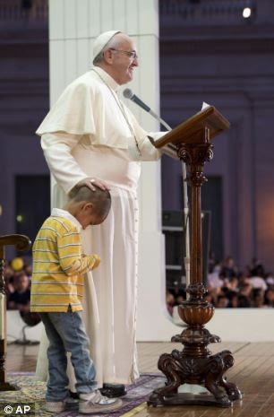 Affectionate: The Pope pats the youngster on the head as he wanders on to the stage
