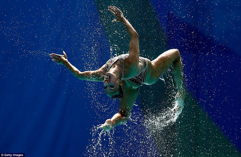 Água voa como um atleta russo é lançado para o ar durante a rotina técnica da natação sychronised