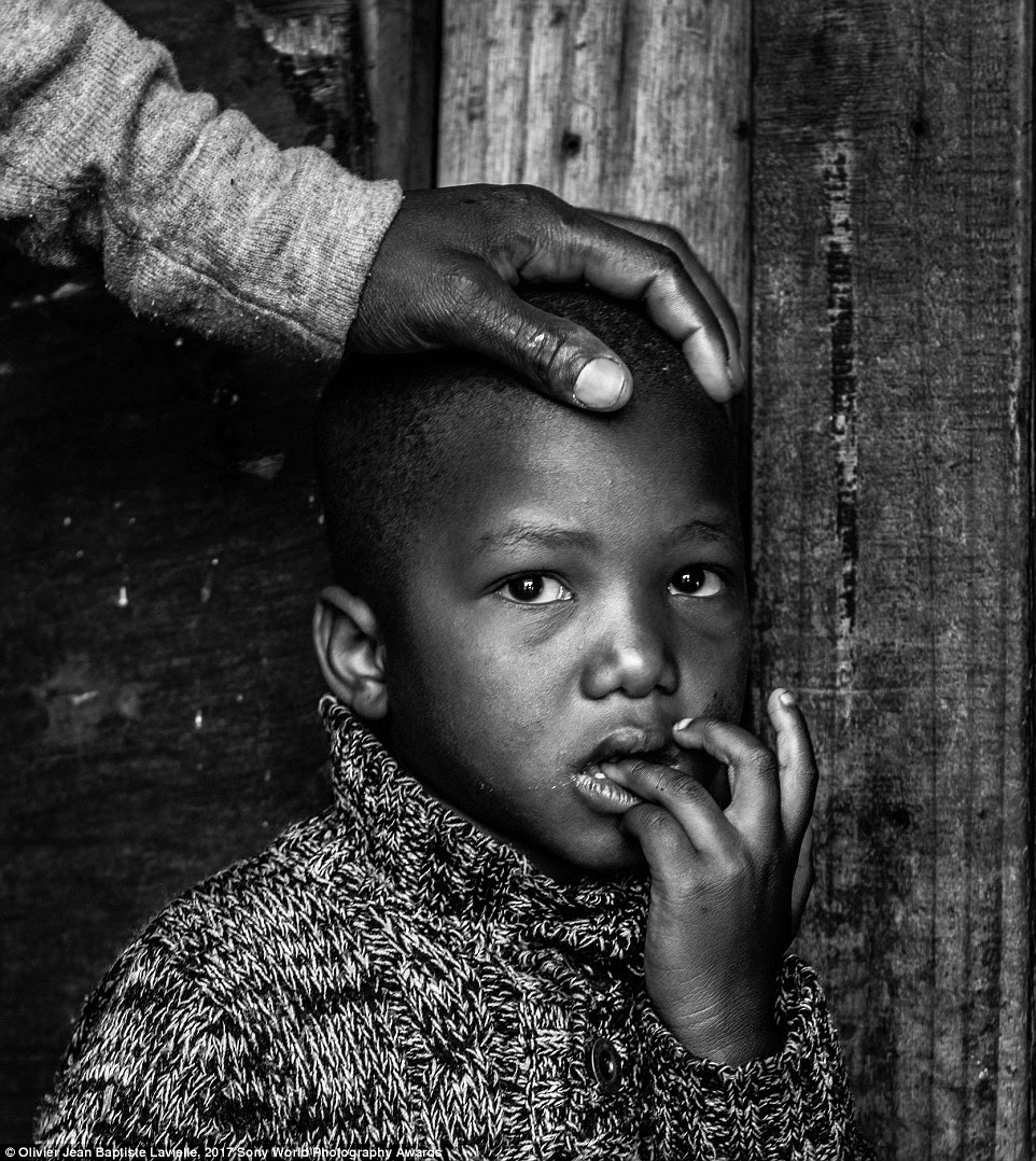 A father places his hand protectively on the head of his son in a township in Cape Town, South Africa. Until the end of the apartheid, these settlements were reserved for non-white residents only
