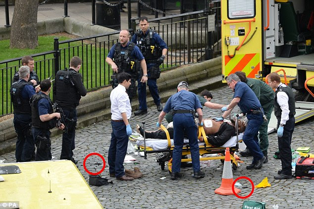 A man, believed to be the attacker, is put on the stretcher and wheeled into an ambulance inside the grounds of Parliament