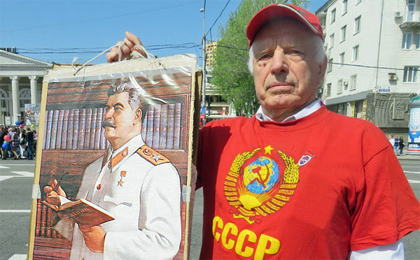 Man poses for photo holding poster of former Soviet Union dictator Joseph Stalin during May Day march in Donetsk, Ukraine, on May 1, 2017 (Photo: Twitter)