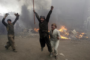 Pakistani men, part of an angry mob, react after burning …