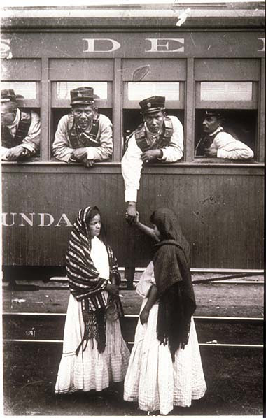 Mexikói forradalom. Revolutionary soldier aboard a train holding the hand of a woman on the ground. Agustín Victor Casasola (1874-1938) fotója. Vö. http://content.cdlib.org/ark:/13030/hb8c601174/?layout=metadata&brand=calisphere