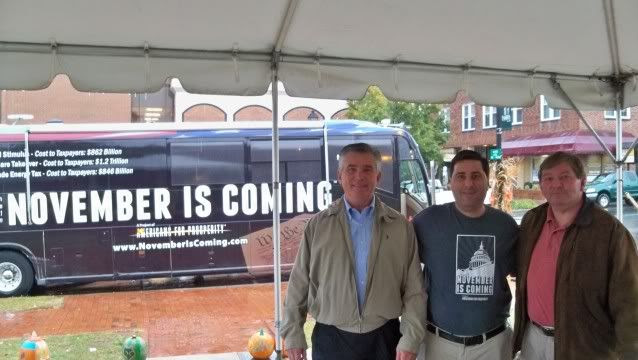 Jim Davis (L) dallas Woodhouse (C) and Gary Dills (R) pose in front of the November is Coming bus in Franklin, NC