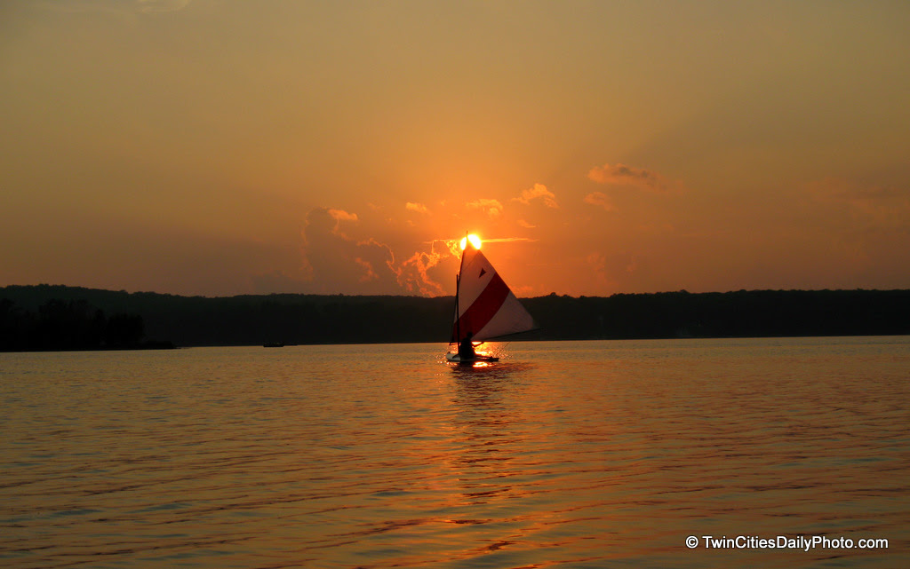 A sailboat crossed directly into the setting sun on Lake Nielson at Tomahawk boy scout camp.