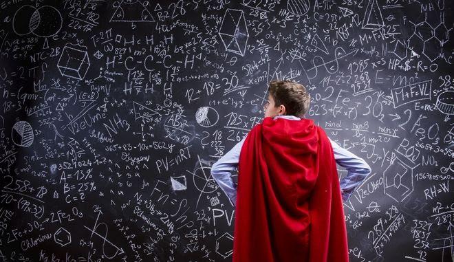 Νεαρό αγόρι μπροστά σε πίνακα με μαθηματικές πράξεις