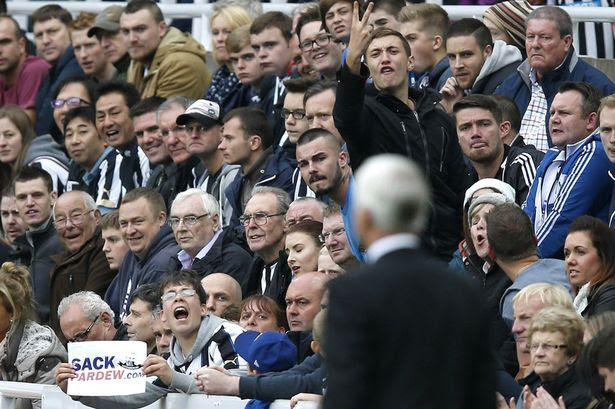 Newcastle United fans gesture towards team manager Alan Pardew