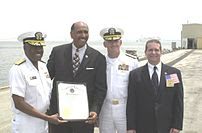 Michael Steele presenting an award to USNS Com...