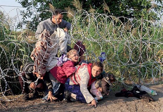 2. Famílias atravessam a cerca farpada na fronteira da Hungria  (Foto: Reuters/Bernadett )