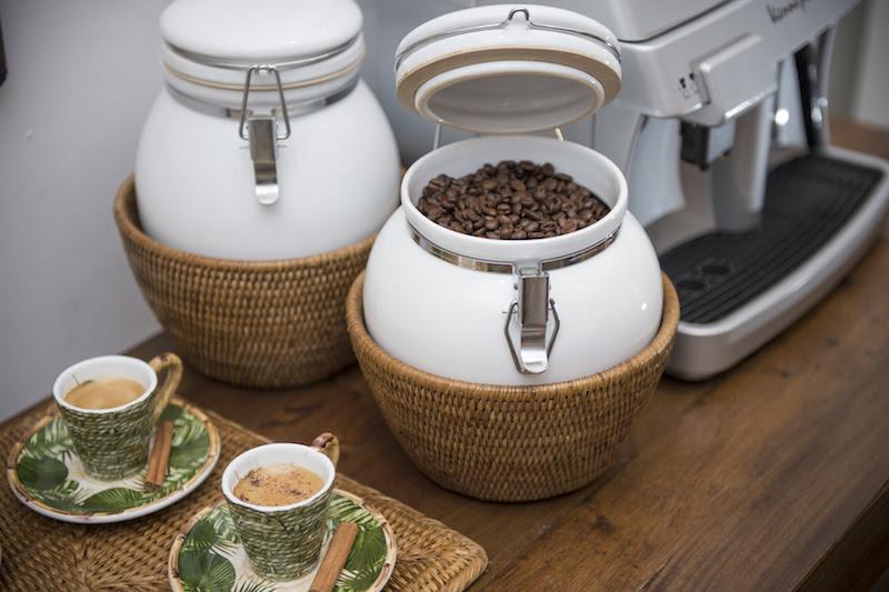 Ao lado da máquina de expresso em grãos, o pote hermético conserva o aroma e o frecor do café com muito charme.