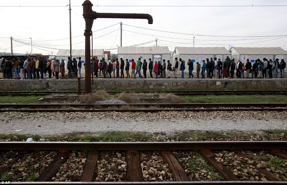 Refugees and migrants queue up for food rations at the transit centre for refugees near northern Macedonian village of Tabanovce