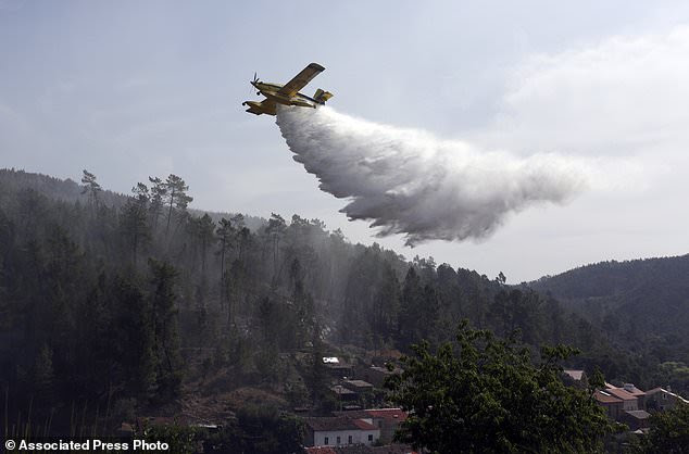 A firefighting plane drops its load to prevent wildfires from reigniting over the village of Agua Formosa, near Vila de Rei, central Portugal, Tuesday, Aug. 15 2017. The small village was evacuated Monday night when raging forest fires approached. Around 3,000 firefighters in Portugal were struggling to put out more than 150 wildfires raging across the country Tuesday, as persistent hot and dry weather stoked the flames, officials said. (AP Photo/Armando Franca)