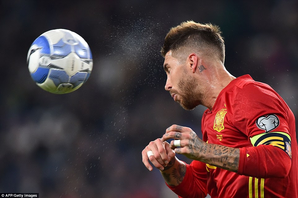 Sweat sprays off the forehead of Spain captain Sergio Ramos as he heads the ball away from danger