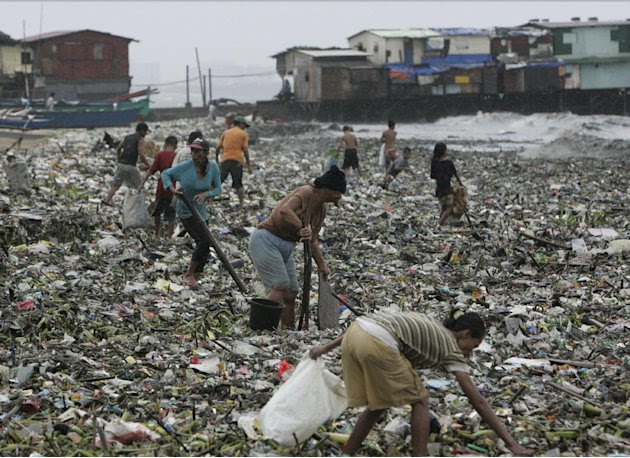 A group of people gather salvagable materials from debris washed ashore due to Typhoon Nanmadol Saturday, Aug. 27, 2011 in Manila, Philippines. Forecasters said the typhoon hit the northeastern tip of