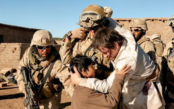 Marcus Luttrell embraces an Afghan boy who helped him seek refuge in an Afghan village prior to the arrival of U.S. forces, in LONE SURVIVOR.