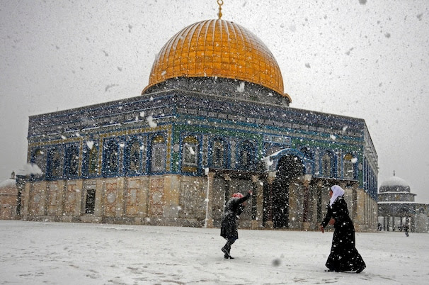 (Mahmoud Illean/ AP ) - Two Palestinian women play with snow outside Al-Aqsa Mosque in Jerusalem on Dec. 12.