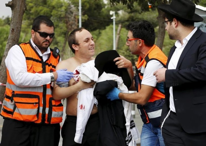 Medics speak to an Israeli man injured during a stabbing attack in Jerusalem October 30, 2015. REUTERS