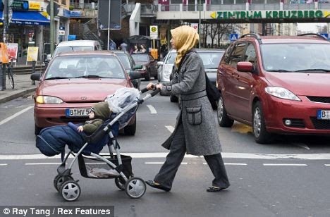 A Muslim wearing a headscarf crosses the road in a predominantly Turkish area of Berlin
