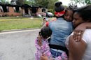 Sisters Brandy McCrary, left, and Breona Montgomery, who are cousins of the five fatal house fire victims, hug neighbors Bonita Beasley, center, and Jennifer Moss, right, in Newnan, Ga., Saturday, April 27, 2013. The fire killed Alonna T. McCrary, 27, as well as her 5-year-old daughter Eriel McCrary and 2-year-old daughter Nikia White, according to Glenn Allen, the Georgia state Insurance commissioner's spokesman. Two other children, Messiah White, 3, and McKenzie Florence, 2, also died. Allen said the two were sleeping over at the home. A fifth child, 11-year-old Nautica McCrary, escaped the burning home and was taken to a hospital to be treated for smoke inhalation. (AP Photo/David Tulis)