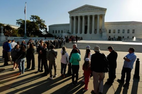 Visitors stand in line to watch arguments on the first day of the new term of the U.S. Supreme Court in Washington