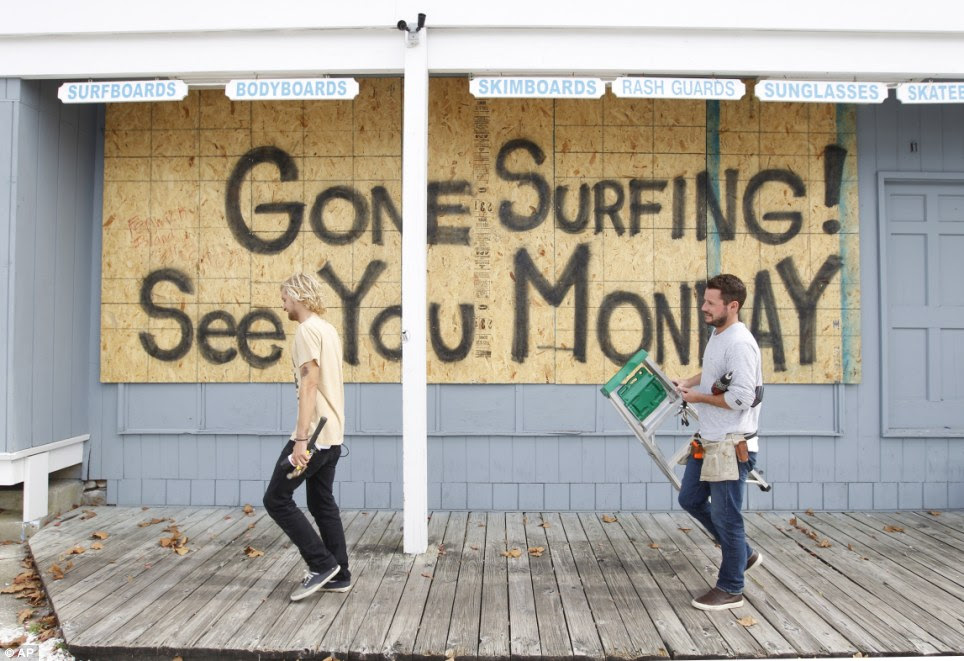 Hurricane humor: Store workers Fletcher Birch, right, and Jay Kleman finish boarding up the windows on a surf store in Ocean City, Maryland