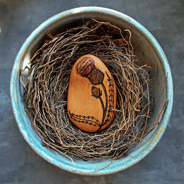 Hand carved pebble brooch