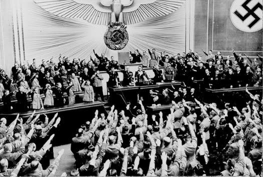 Discorso di Hitler al Reichstag. La svastica, antico simbolo magico della tradizione indoeuropea, era stata assunta dall'inizio del XX secolo come emblema dai movimenti antisemiti, e venne quindi adottata dai nazisti.