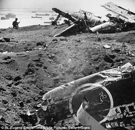 Aircraft wreckage on beach (with American fleet in background) following US Marines' fierce battle against Japanese for Iwo Jima during WWII.