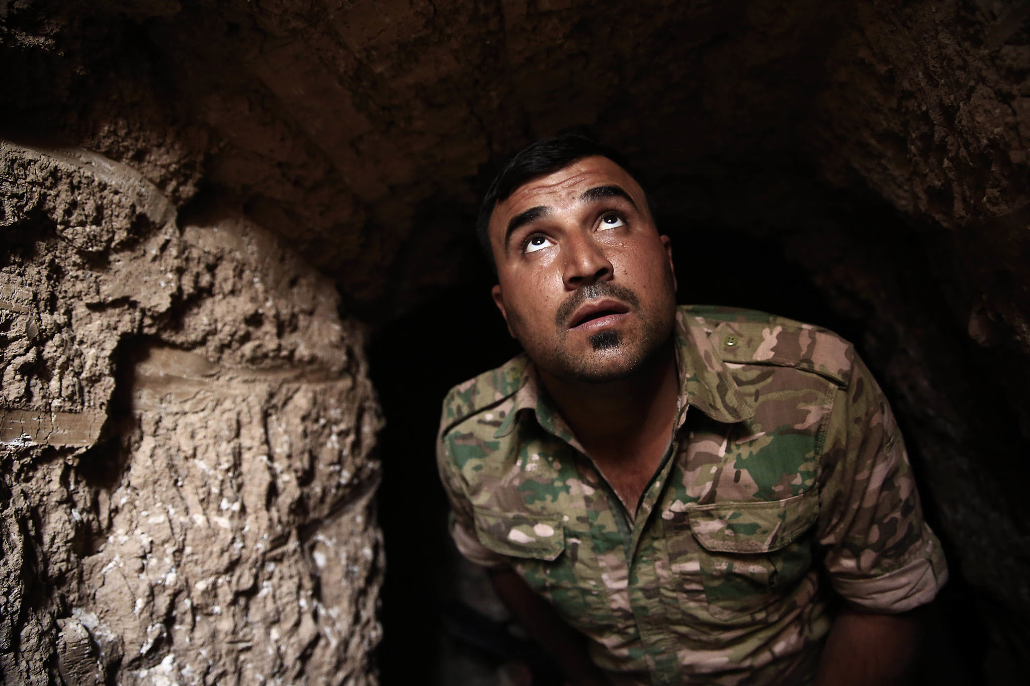 A peshmerga fighter looks out of the entrance of an underground tunnel built by Islamic State fighters, Tuesday, Oct. 18, 2016. The Kurdish forces found the tunnel in the town of Badana that was liberated from the Islamic State group on Monday. The fighters built tunnels under residential areas so they could move without being seen from above to avoid airstrikes. (AP Photo/Bram Janssen)