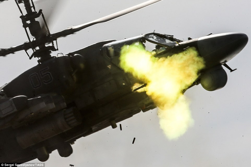 A Kamov Ka 52 Alligator helicopter fires rounds at a practice target during the drills. The spent shell casings can be seen dropping from the base of the aircraft