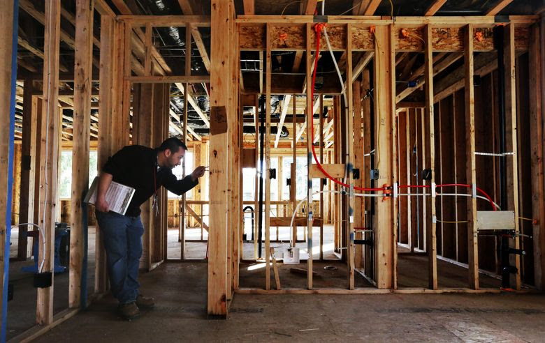 Joe Benson, an electrical inspector with the state Department of Labor and Industries, checks wiring in new construction at a Kent subdivision. If something is amiss, there will be a return visit to make sure the problem is fixed. Electrical inspectors are among the job classes in line for larger-than-average raises under labor contracts now before state lawmakers.  (Alan Berner/The Seattle Times)