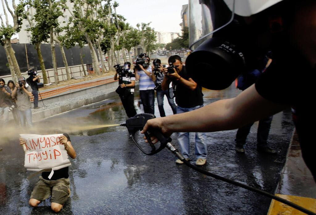 The same protester holding the 'Chemical Tayyip [Erdogan]' sign pepper sprayed at close range.