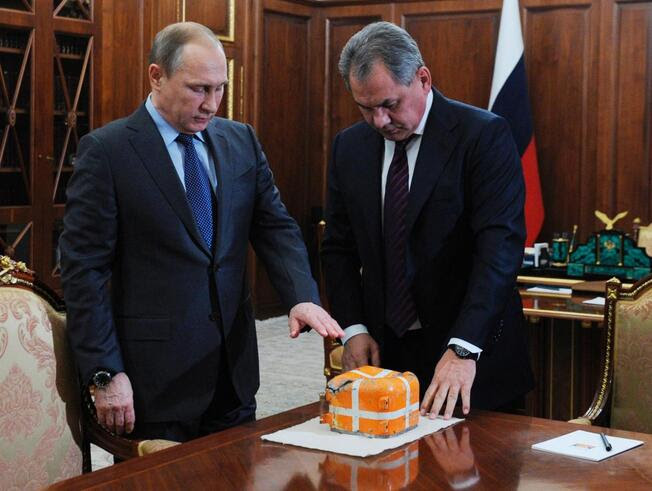 Russian President Vladimir Putin, left, and Defense Minister Sergei Shoigu, examine a flight recorder from the Russian warplane shot down by a Turkish jet on Nov. 24, in the Novo-Ogaryovo residence outside Moscow, Russia, Tuesday, Dec. 8, 2015. Shoigu said Syrian and Russian troops had recovered the plane's flight recorder, and Putin ordered it to be studied in the presence of foreign experts.